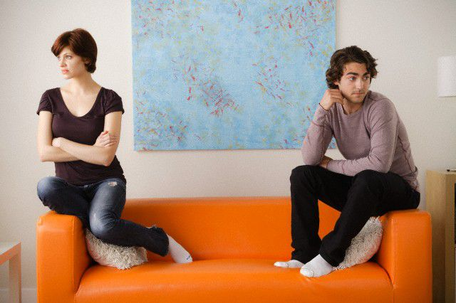 2012, Los Angeles, California, USA --- USA, California, Los Angeles, Young couple sitting on sofa  --- Image by © Tetra Images/Corbis